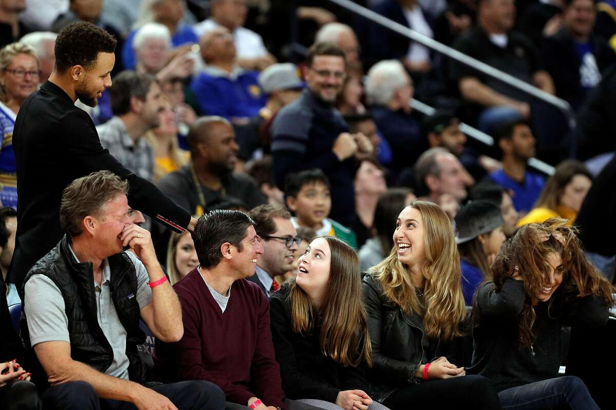 Stephen Curry (30) checks on a fan who was hit by a loose ball in the first half as the Golden State Warriors played the Utah Jazz at Oracle Arena in Oakland, Calif., on Wednesday, December 27, 2017.