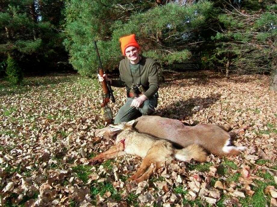 The writer's son, Josh Lounsbury, shows a Thumb doe and coyote which he bagged from the same ladder-stand, minutes apart, during a regular firearm deer season. (Tom Lounsbury/Hearst Michigan)