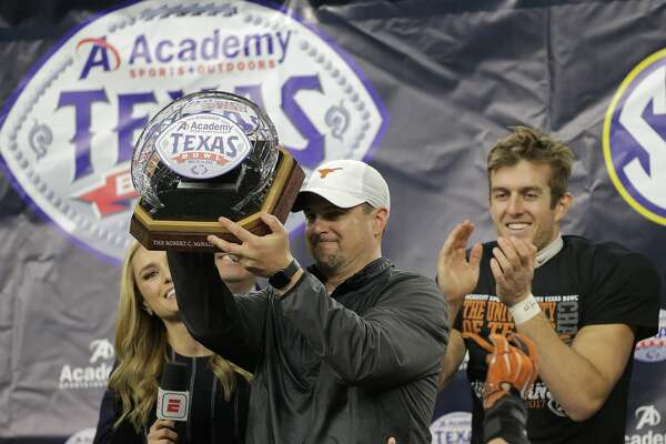 Texas Longhorns head coach Tom Herman holds up the trophy with Texas Longhorns punter Michael Dickson (13) behind him after The Academy Sports + Outdoors Texas Bowl against Missouri at NRG Stadium on Wednesday, Dec. 27, 2017, in Houston. Texas won the game 33-16. ( Elizabeth Conley / Houston Chronicle )