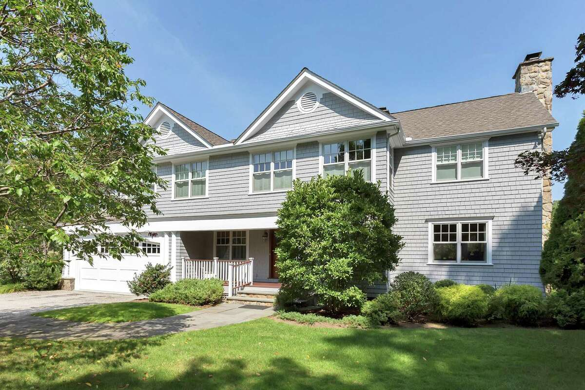 The 12-room custom colonial gray shingle house at 25 Five Mile River Road sits on a level property of almost a half acre.