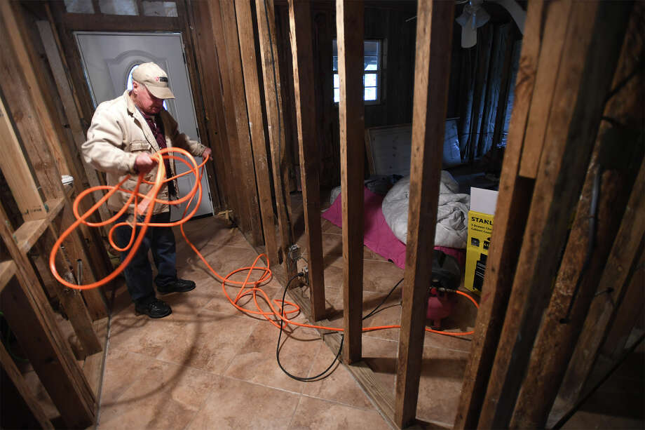 David Long picks up an air hose line at his Rose City home on Thursday. Long is rebuilding his home from Tropical Storm Harvey. Photo taken Thursday, December 27, 2017 Guiseppe Barranco/The Enterprise Photo: Guiseppe Barranco, Photo Editor / Guiseppe Barranco ©