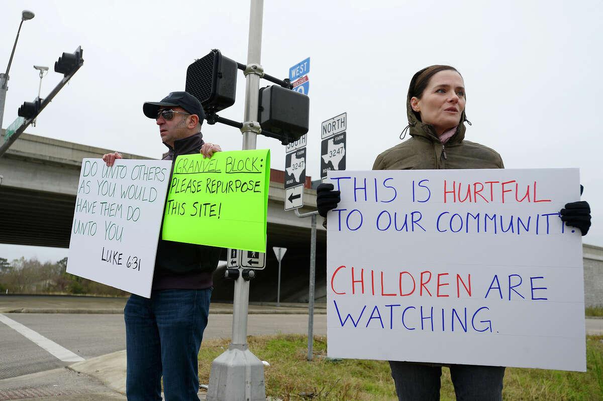 Jeremy and Tracie Parzen hold protest signs near the Confederate Memorial of the Wind in Orange on Wednesday. The unfinished memorial is being built by the Sons of Confederate Veterans next to Interstate 10. Photo taken Wednesday 12/27/17 Ryan Pelham/The Enterprise