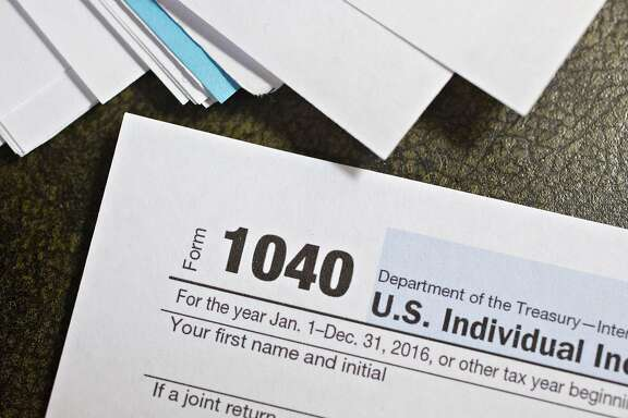 U.S. Department of the Treasury Internal Revenue Service (IRS) 1040 Individual Income Tax forms for the 2016 tax year are arranged for a photograph in Tiskilwa, Illinois, U.S., on Monday, Dec. 18, 2017. This week marks the last leg of Republicans' push to revamp the U.S. tax code, with both the�House�and Senate planning to vote by Wednesday on final legislation before sending it to President�Donald Trump. Photographer: Daniel Acker/Bloomberg