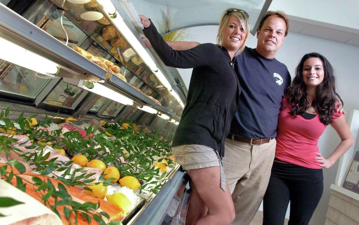 Gary Swanson and his daughters Lynette, left, and Larissa pose in front of the display case at Swanson's Fish Market in Fairfield in 2010. The family-owned business will be closing for good on New Years Eve.