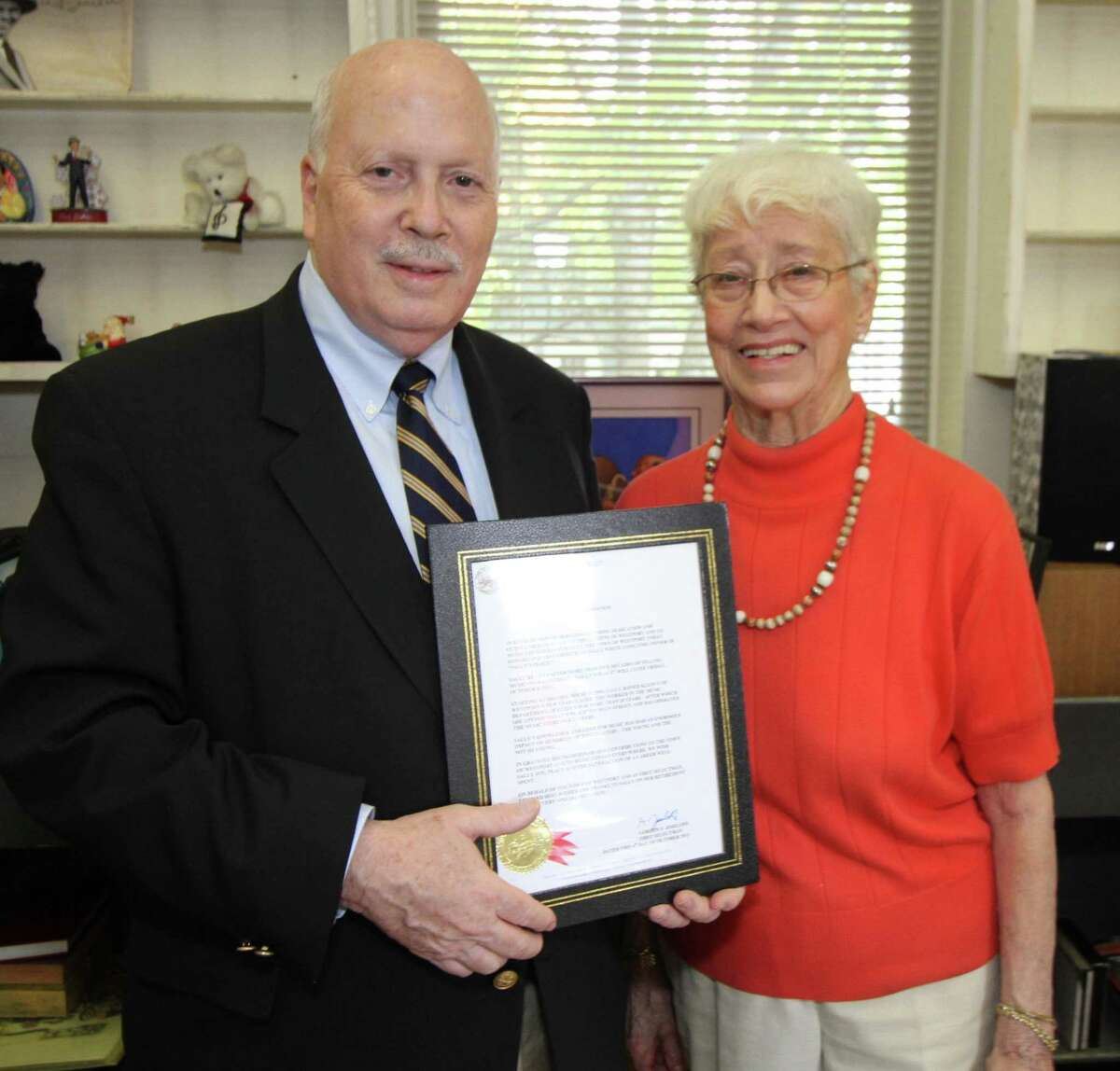 First Selectman Gordon Joseloff displays a commendation from the town to Sally White, before presenting it to her at town hall on Thursday, Oct. 4. White provided music to several generations of Westporters over a half century before closing her Sally's Place record shop this summer.