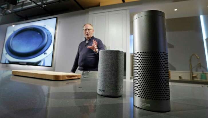 FILE - In this Wednesday, Sept. 27, 2017, file photo, David Limp, senior vice president of Devices and Services at Amazon, displays a new Echo, left, and an Echo Plus during an event announcing several new Amazon products by the company, in Seattle. Internet-connected lights, locks and laundry machines are on the cusp of broadening beyond tech-savvy enthusiasts. Voice-activated speakers such as Amazon's Echo and Google Home are partly the reason. The more people use such speakers, the more they seek out what else they can do.