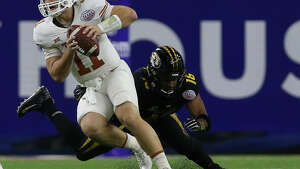 Texas Longhorns quarterback Sam Ehlinger (11) dodges a sack from Missouri Tigers defensive lineman Marcell Frazier (16) during the third quarter of the 2017 Academy Sports + Outdoors Texas Bowl game at NRG Stadium on Wednesday, Dec. 27, 2017, in Houston.