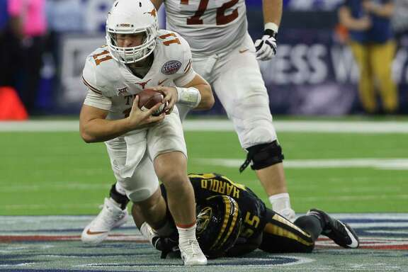 Texas Longhorns quarterback Sam Ehlinger (11) is brought down by Missouri Tigers defensive lineman Jordan Harold (55) while running the ball during the fourth quarter of the 2017 Academy Sports + Outdoors Texas Bowl game at NRG Stadium on Wednesday, Dec. 27, 2017, in Houston. The Texas Longhorns defeated the Missouri Tigers 33-16.