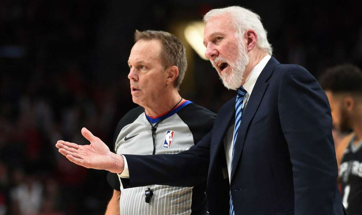 Spurs coach Gregg Popovich talks to referee Bill Spooner during a Dec. 20, 2017 game in Portland, Ore. Popovich has been outspoken off the court too this year, talking at length about political and social issues.