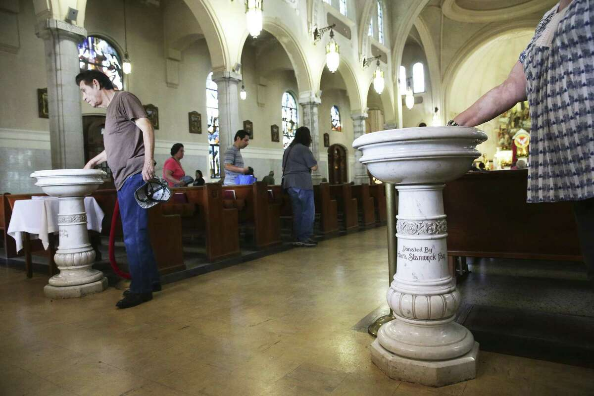 Church goers leave and bless themselves with holy water as they near the back of the church at the Basilica of the National Shrine of the Little Flower on June 6, 2017.