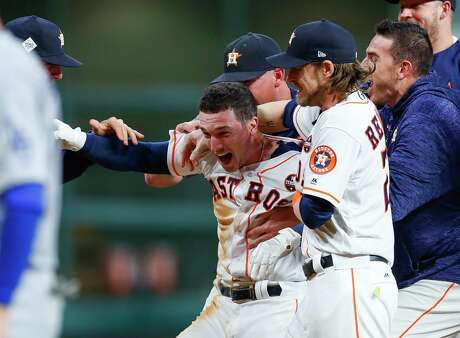 Houston Astros third baseman Alex Bregman (2) is surrounded by his teammates after hitting a walk off single that drove in left fielder Derek Fisher (21) to give the Astros a 13-12 victory over the Los Angeles Dodgers in the tenth inning of Game 5 of the World Series at Minute Maid Park on Monday, Oct. 30, 2017, in Houston. ( Brett Coomer / Houston Chronicle )