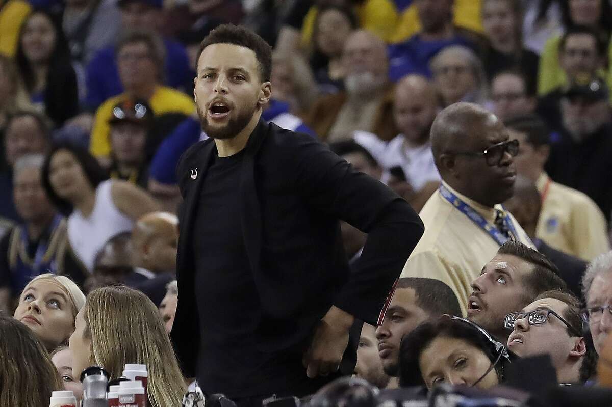 Injured Golden State Warriors guard Stephen Curry watches from the bench during the first half of the team's NBA basketball game against the Utah Jazz in Oakland, Calif., Wednesday, Dec. 27, 2017. (AP Photo/Jeff Chiu)