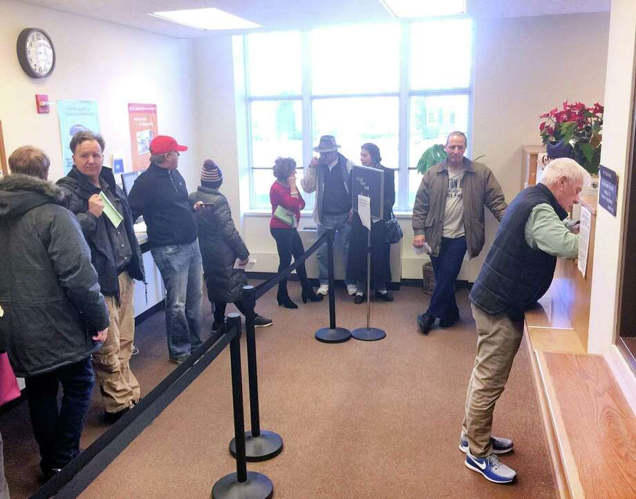 Greenwich resident Ray Johnson, right, pays taxes at Greenwich Town Hall in Greenwich, Conn., Thursday, Dec. 28, 2017. According to a posted sign in the tax collector's office, no advanced payment of taxes can be accepted, only January 2018 installments can be paid. Photo: Bob Luckey Jr. / Hearst Connecticut Media / Greenwich Time