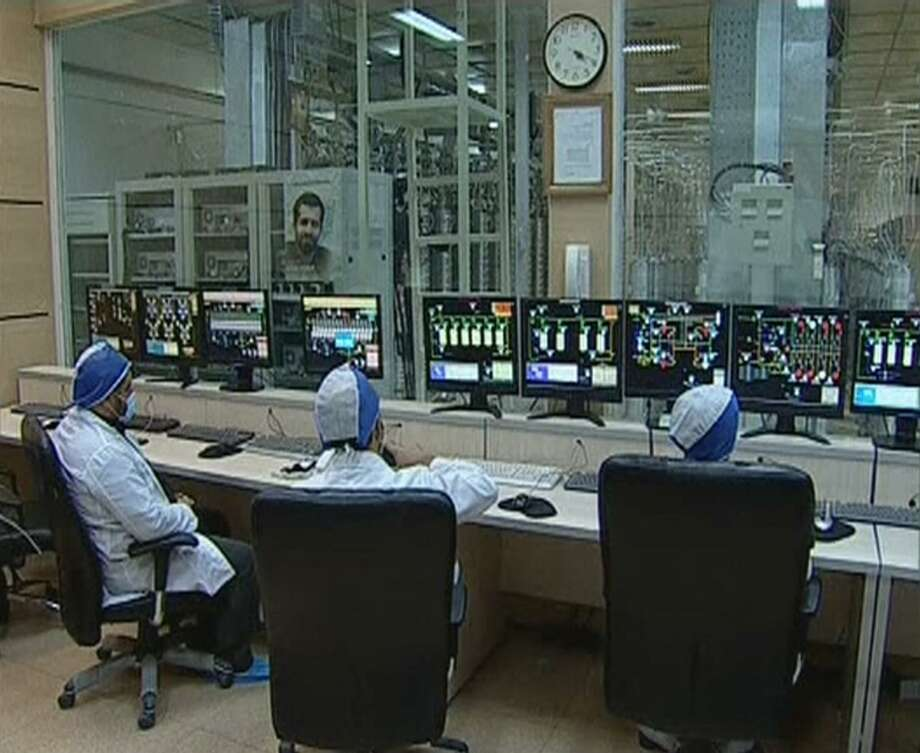 Workers at the Iranian nuclear enrichment facility at Natanz in an undated handout frame grab. The Stuxnet computer worm temporarily disabled 1,000 centrifuges at the facility, prompting Iran to become a cyber threat — including to the U.S. Photo: IRANIAN TELEVISION /New York Times / IRANIAN TELEVISION