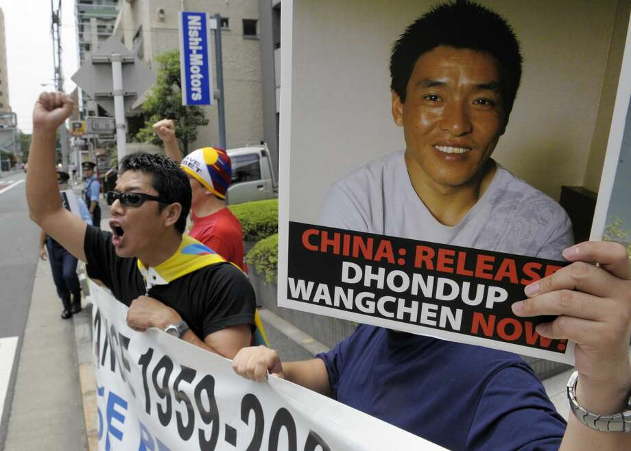 "FILE-- Protesters of ""Students for a Free Tibet Japan"" shout slogans during a demonstration to demand the release of arrested Tibetan movie director Dhondup Wangchen (poster) in front of the Chinese embassy in Tokyo on August 1, 2009. Wangchen, a 43-year-old Tibetan filmmaker imprisoned by the Chinese government for making a short documentary about Tibetan opposition to the 2008 Beijing Olympics has managed to flee China and arrive in San Francisco, his supporters have announced. Photo: TOSHIFUMI KITAMURA/AFP/Getty Images"