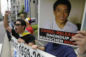 """Protesters of """"Students for a Free Tibet Japan"""" shout slogans during a demonstration to demand the release of arrested Tibetan movie director Dhondup Wangchen (poster) in front of the Chinese embassy in Tokyo on August 1, 2009. Wangchen has been jailed in China since March 2008 after secretly making a documentary film in Tibet and is due to stand trial soon.  AFP PHOTO/TOSHIFUMI KITAMURA (Photo credit should read TOSHIFUMI KITAMURA/AFP/Getty Images)"""
