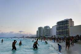 Beachgoers wade on the beach in Cancun, Mexico, on April 4, 2015. (MUST CREDIT: Cassi Alexandra/Bloomberg)