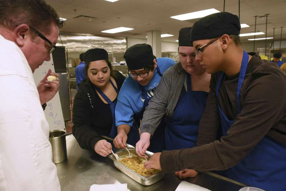 Howie Velie, director of education at the Culinary Institute of America (from left), works with Destiny Benavidez, John Lopez, Faith Mitchell and Hector Benavides in the Lanier High School culinary program. Photo: Photos By Billy Calzada /San Antonio Express-News / San Antonio Express-News