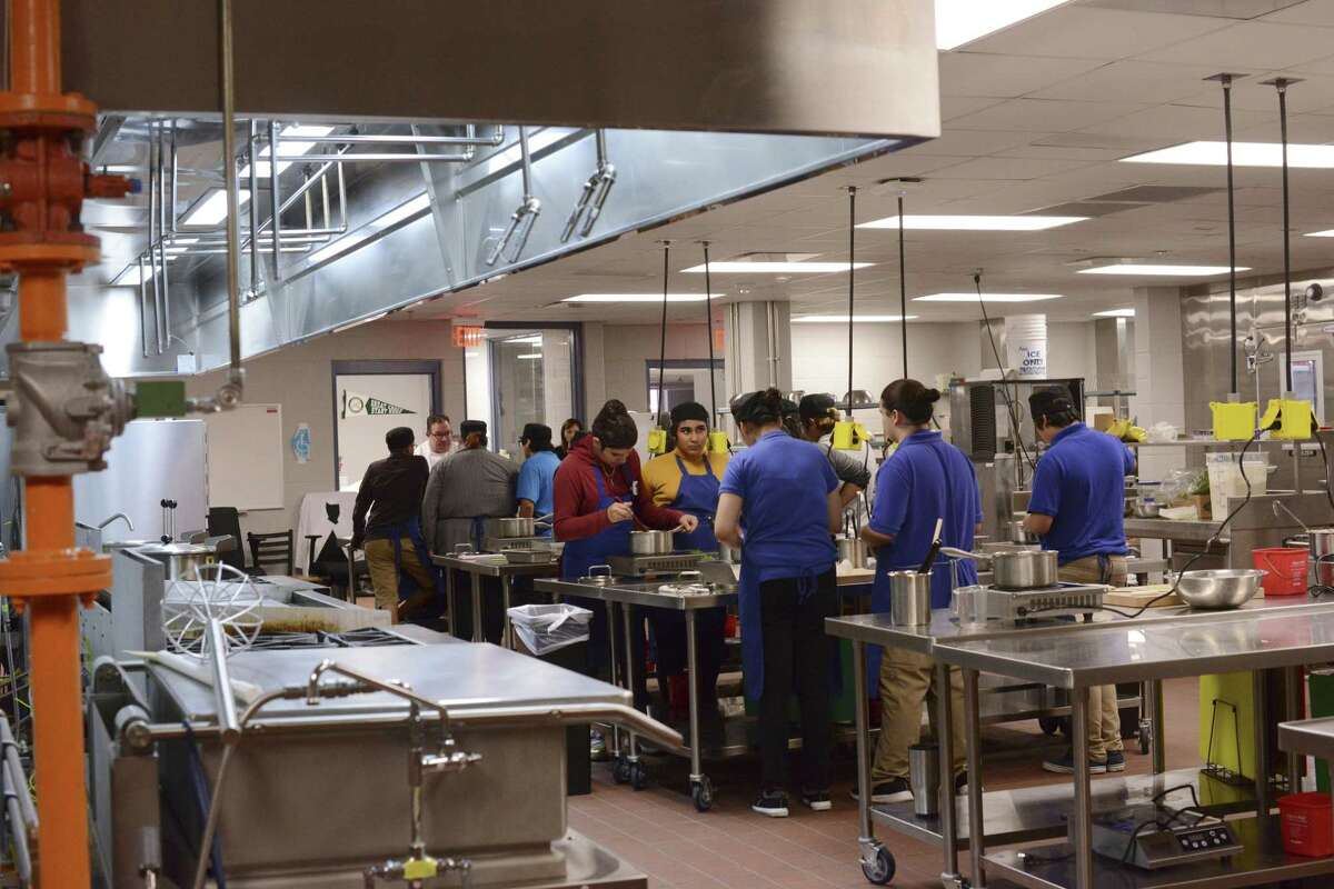 Students prepare cauliflower gratin and creamed spinach in the culinary program at Lanier High School on Nov. 29, 2017.