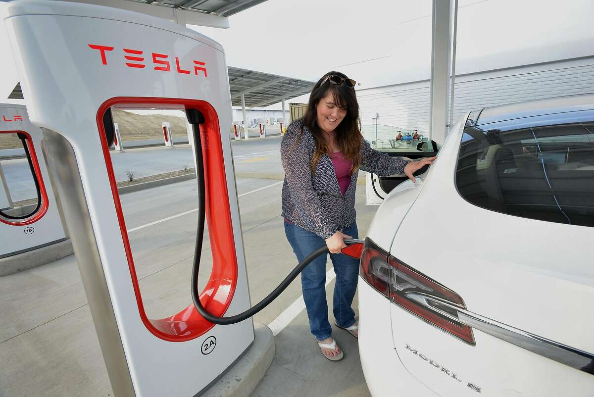Carolyn Lowe, 47, of Fairfield, plugs a supercharger into her sister's Tesla during a stop for lunch on their way home from Beverly Hills on Friday, December 15, 2017 at the Tesla Supercharger station along I-5 in Kettleman City, Calif. The Tesla Supercharger station has 40 Superchargers available exclusively for Tesla owners, a 24/7 customer lounge, restrooms, free WiFi, a coffee bar, vending machines, a children's play area and an outdoor pet run.