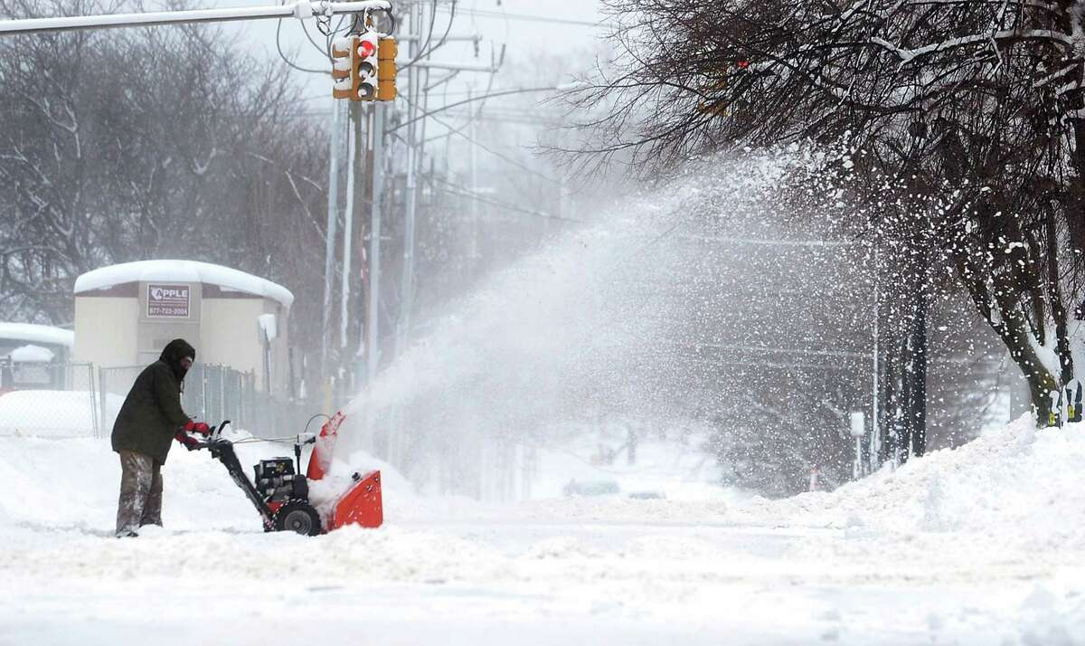 A man clears snow on Tuesday, Dec. 26, 2017, in Erie, Pa. The National Weather Service office in Cleveland says Monday's storm brought 34 inches of snow, an all-time daily snowfall record for Erie. (Greg Wohlford/Erie Times-News via AP)