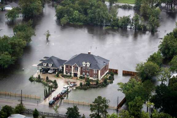 Floodwaters from Tropical Storm Harvey surround a home on Tuesday, Aug. 29, 2017, in Houston. ( Brett Coomer / Houston Chronicle )