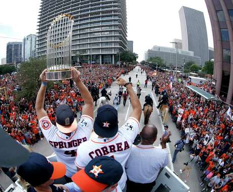 Houston Astros' World Series MVP George Springer, left, with World Series trophy, Carlos Correa, left, Houston Mayor Sylvester Turner ride on top of a fire truck celebrate during a parade honoring the World Series baseball champions Friday, Nov. 3, 2017, in Houston. (Karen Warren/Houston Chronicle)