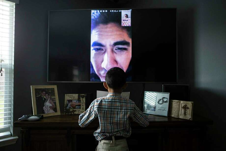 Jose Escobar watches his son Walter Escobar, 7, open his graduation gifts using a chat video application from El Salvador, Tuesday, May 30, 2017, in Houston. ( Marie D. De Jesus / Houston Chronicle ) Photo: Marie D. De Jesus, Staff / © 2017 Houston Chronicle