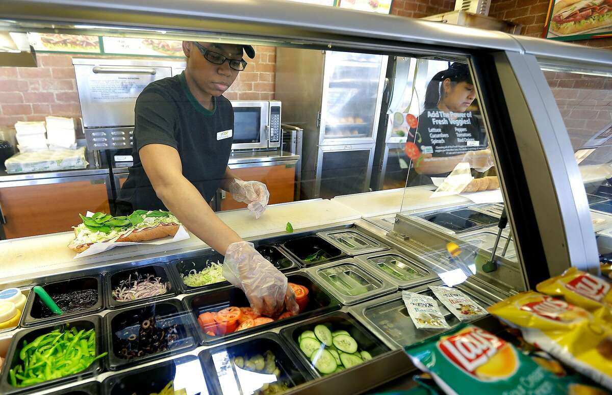 In this March 3, 2015 photo, workers make sandwiches at a Subway sandwich franchise in Seattle.