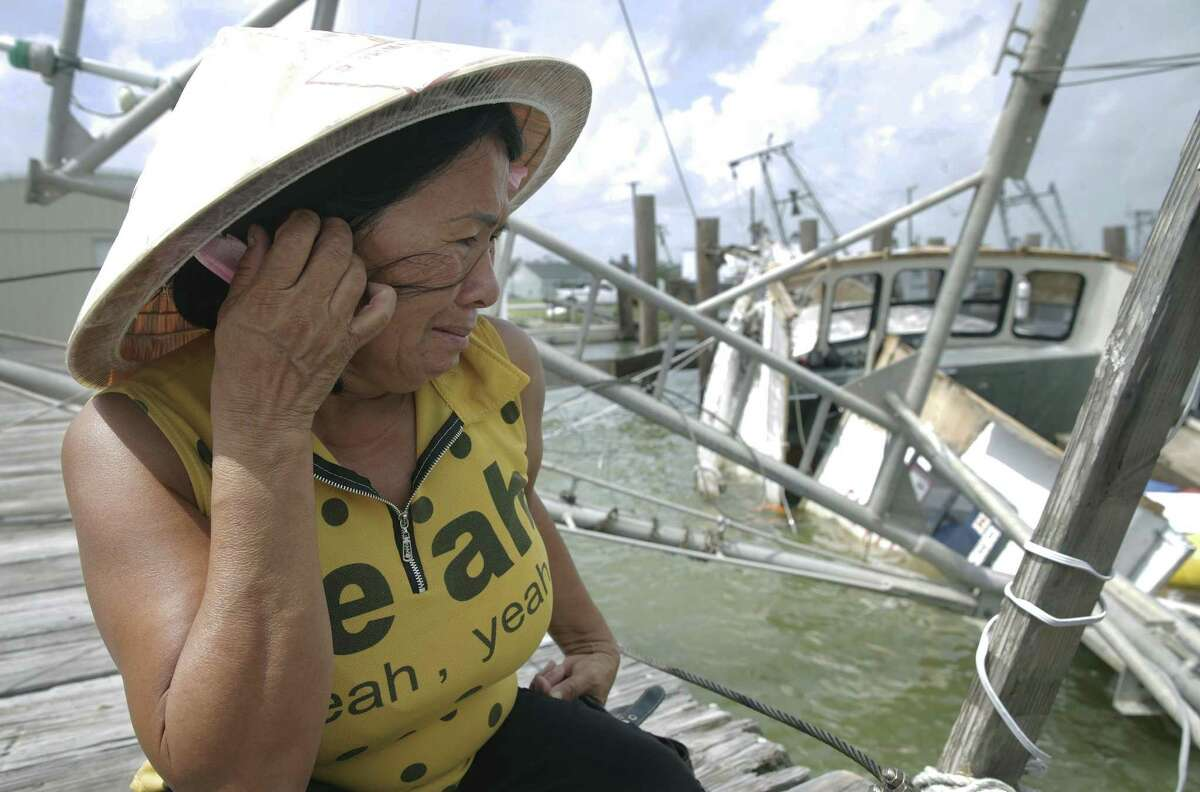 Le An Thi holds back tears while overlooking her family's shrimping boat as it rests in the water after sinking at the dock as Rockport tries to recover from Hurricane Harvey devastation on September 26, 2017. The family of the owner had just invested $75,000 three days prior to seeing it destroyed.