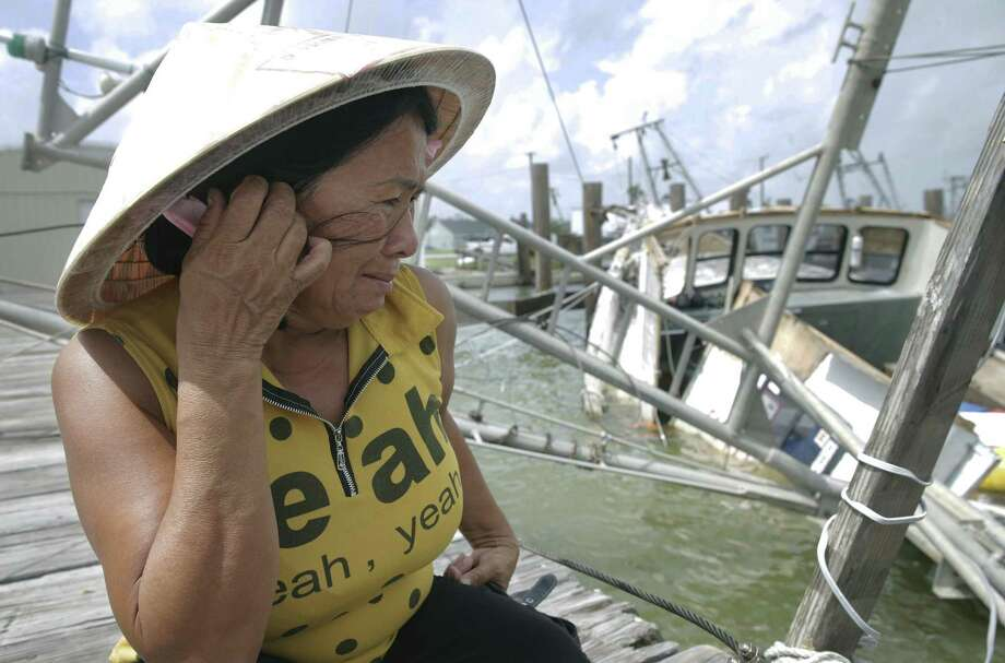 Le An Thi holds back tears while overlooking her family's  shrimping boat as it rests in the water after sinking at the dock as Rockport tries to recover from Hurricane Harvey devastation on September 26, 2017.  The family of the owner had just invested $75,000 three days prior to seeing it destroyed. Photo: Tom Reel, Staff / San Antonio Express-News / 2017 SAN ANTONIO EXPRESS-NEWS