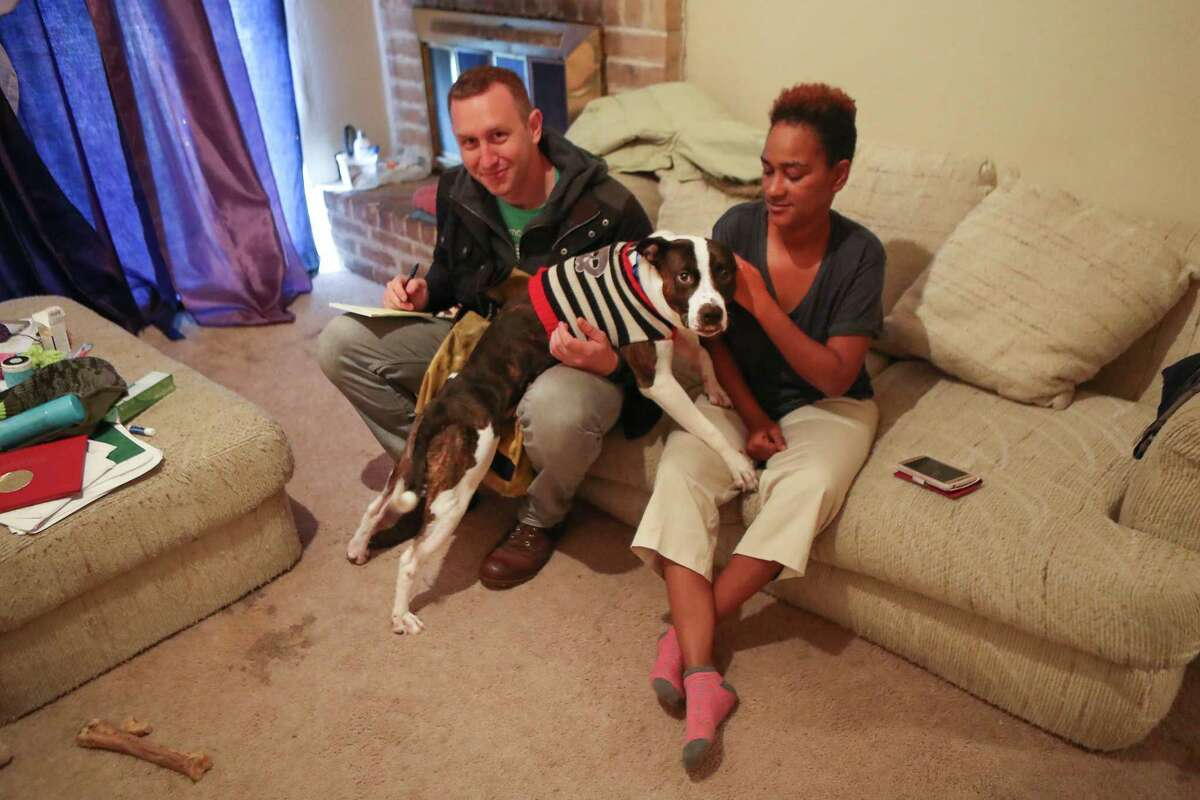 """Houston Chronicle Reporter St. John Barned-Smith attempts to interview Cherika Argus, one of the victims of the Briscoe's Place fire, as he dog, """"Roscoe"""" wants some attention Wednesday, Dec. 20, 2017, in Houston. ( Steve Gonzales / Houston Chronicle )"""