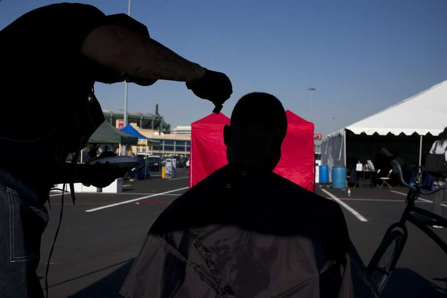 A homeless man, who declined to give his name, gets a free haircut in the parking lot at Angel Stadium in Anaheim. Photo: Jae C. Hong, Associated Press