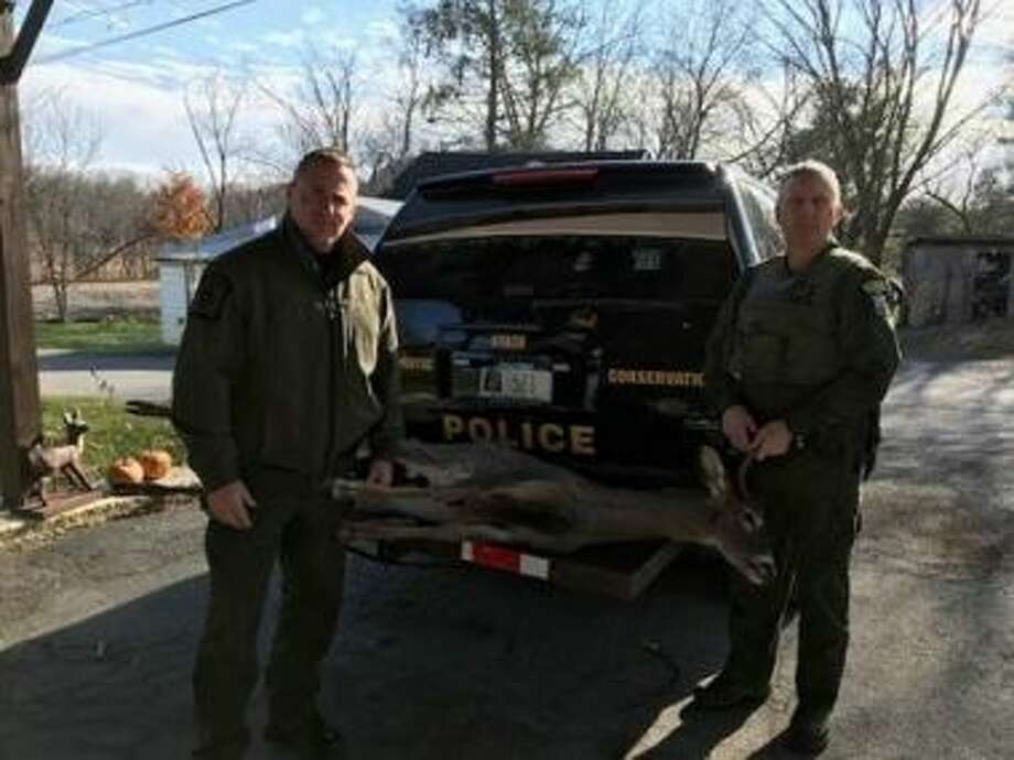 State Environmental Conservation Officers Lou Gerrain and Alan Brassard pose with a deer that was improperly tagged in Queensbury. Photo: State Department Of Environmental Conservation