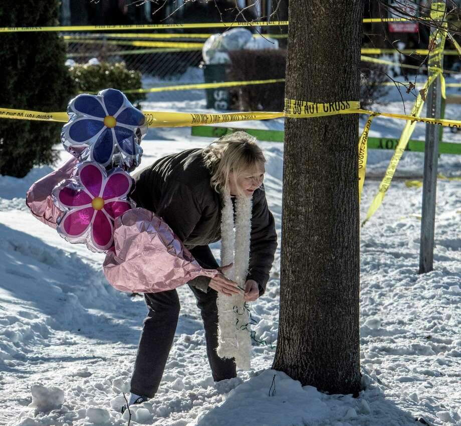 A woman, who asked not to be identified,  brings a bouquet of balloons to start a makeshift memorial near the home at 158 Second Ave. on Thursday, Dec 28, 2017, the scene of a quadruple murder earlier in the week in Troy, N.Y.  (Skip Dickstein/ Times Union) Photo: SKIP DICKSTEIN / 20042523A