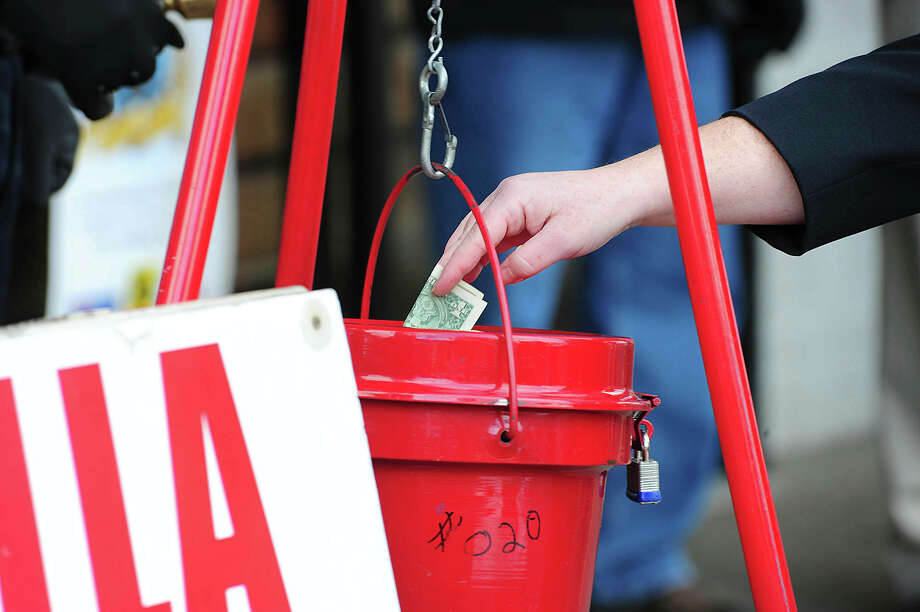 FILE - In this Nov. 22, 2017, file photo, a patron donates money in a Salvation Army red kettle in Wilkes-Barre, Pa. In this season of giving, charity seems to be getting an extra jolt because the popular tax deduction for charitable donations will lose a lot of its punch.  (Mark Moran/The Citizens' Voice via AP) Photo: Mark Moran, MBI / The Citizens' Voice