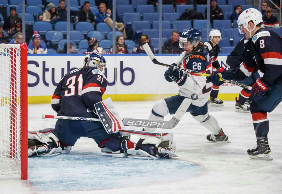 U.S. goalie Joseph Woll makes a save on Slovakia's Milos Roman, center, as United States' Adam Fox, right, defends during the second period of an IIHF world junior hockey championships game in Buffalo, N.Y., Thursday, Dec. 28, 2017. (Mark Blinch/The Canadian Press via AP) Photo: Mark Blinch / Mark Blinch