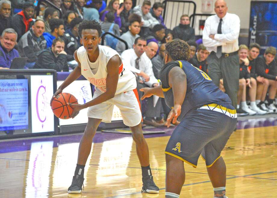 Edwardsville junior Jaylon Tuggle, left, looks to pass the ball while being guarded by a Belleville Althoff player during Thursday's game at the Collinsville Holiday Classic.
