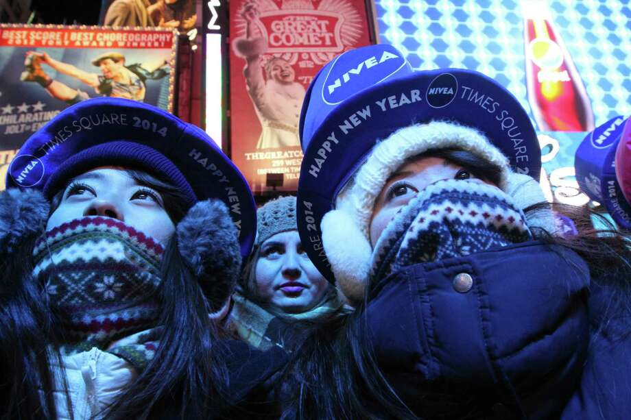 Bundled against the cold, Yuri Asano, left, and her sister Mami Asano, right, both from Aichi, Japan, take part in the New Year's Eve festivities Tuesday Dec. 31, 2013 in New York's Times Square. On Dec. 31, 2017, a low of 11 degrees for Times Square. Accuweather says if the temperature at midnight is 14 degrees or lower, it would be one of the top three lowest New Year's Eve midnight temperatures on record in New York City, and that appears likely on Sunday night. The coldest New Year's Eve in Times Square was in 1917 with 1 degrees, followed by 11 in 1962. Photo: Tina Fineberg / Associated Press / FR73987 AP