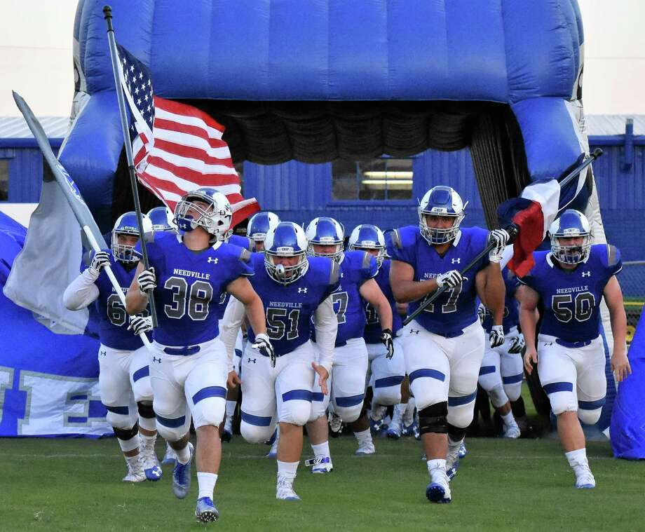 Running onto the field Friday night with their Blue Jay pride in full force, members of the Needville High School varsity football team were ready for the season to finally began. From left are Mason Pace with the Needville Blue Jays flag, Quade Miller with the American flag, Trevor Short, Cameron Harris with the Texas flag, and Trystan Short. Photo: Needville ISD Communications
