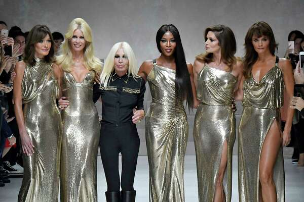 Carla Bruni, from left, Claudia Schiffer, Donatella Versace, Naomi Campbell, Cindy Crawford and Helena Christensen walk the runway at the Versace Ready to Wear Spring/Summer 2018 fashion show.