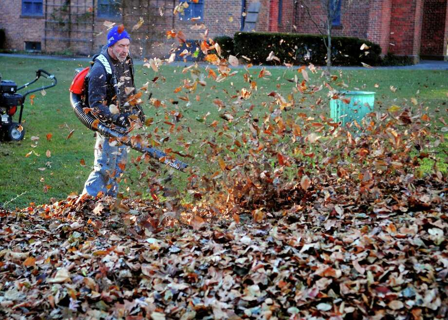 Larry Varone, an employee of Nael's Fresh Start landscaping, uses a leaf blower to move leaves off the grass at St. Paul's Episcopal Church in Fairfield, Conn., on Thursday, Dec. 21, 2017. Photo: Christian Abraham / Hearst Connecticut Media / Connecticut Post