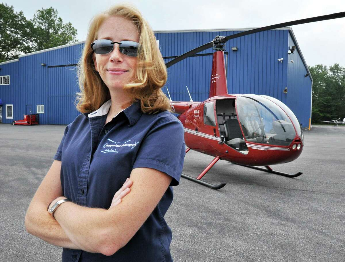 Pilot Heather Howley of Independent Helicopters with her Robinson R44 helicopter at Saratoga County Airport in Ballston Spa, NY Wednesday July 10, 2013. (John Carl D'Annibale / Times Union)