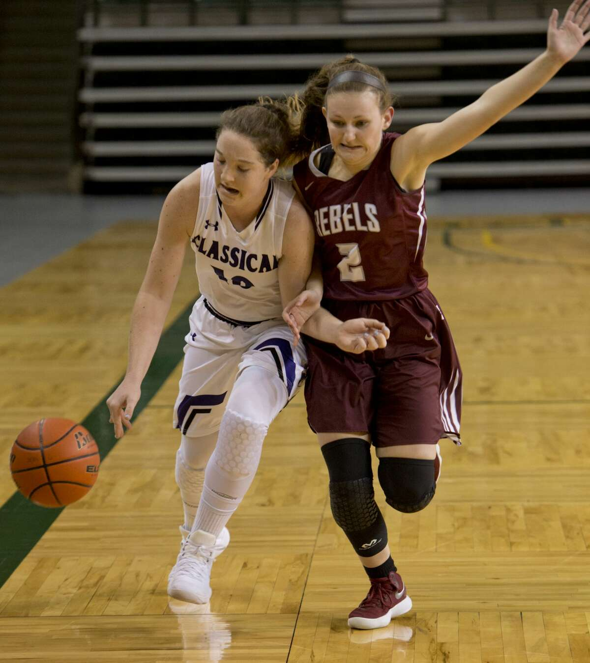 Midland Classical Academy's Leia Beattie brings the ball down the court as Midland Lee's Karigan Edwards defends 12/29/17 at the Byron Johnston Holiday Classic tournament. Tim Fischer/Reporter-Telegram