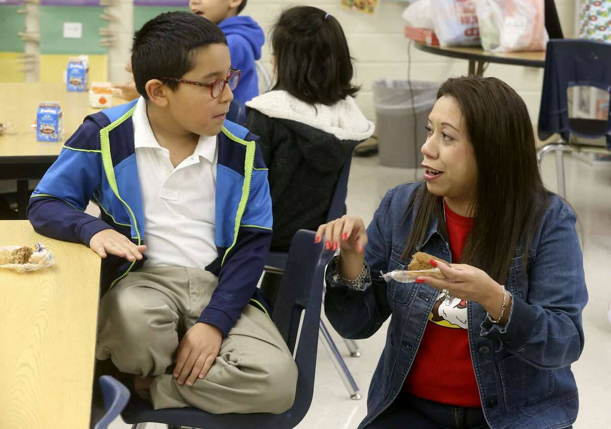 Student Nathaniel Hernandez,8, (left) has breakfast Wednesday morning December 20, 2017 with second grade teacher Patricia Tristan (right) in her classroom at De Zavala Elementary school on San Antonio's West Side. The San Antonio Independent School District is ranked highly statewide for its school food program, mostly due to serving breakfast in class which drives student participation rates higher.