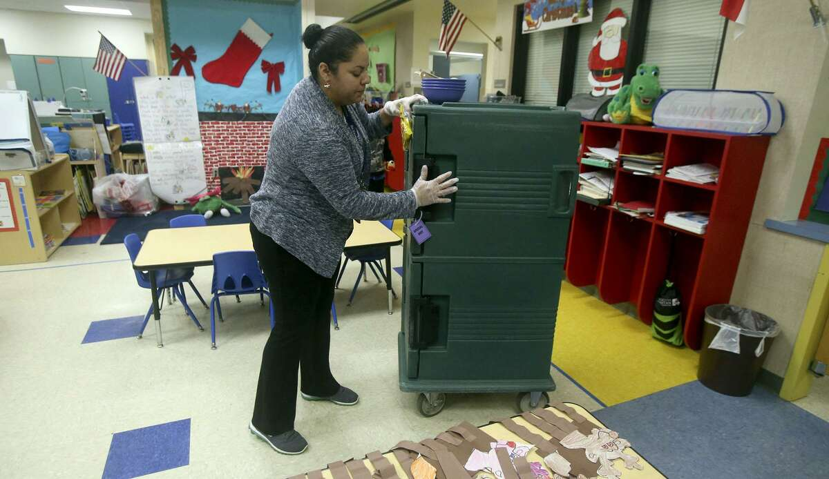 Juanita Maldonado transports breakfast food Wednesday morning December 20, 2017 to a classroom at De Zavala Elementary school on San Antonio's West Side. The San Antonio Independent School District is ranked highly statewide for its school food program, mostly due to serving breakfast in class which drives student participation rates higher.