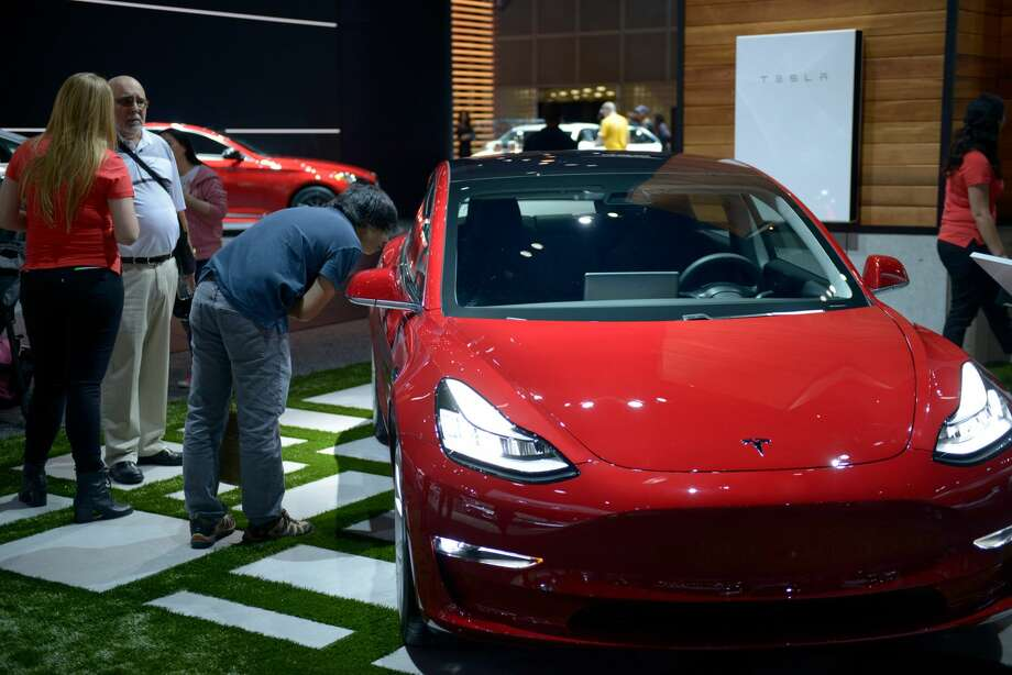 People inspect the Tesla Model 3 as it sits on display at the Los Angeles Auto Show in the Los Angeles Convention Center in Los Angeles on Dec. 1, 2017. Photo: Anadolu Agency/Getty Images