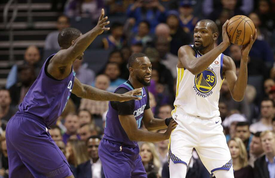 Golden State Warriors' Kevin Durant, right, looks to pass as he is guarded by Charlotte Hornets' Kemba Walker, center, and Marvin Williams during the first half of an NBA basketball game in Charlotte, N.C., Wednesday, Dec. 6, 2017. (AP Photo/Chuck Burton) Photo: Chuck Burton, Associated Press
