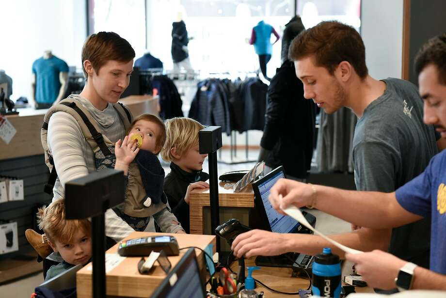 Sale associate Jake Garrissere, right, helps customer Esther Crane of San Francisco and her children Tate (9 months), Aleksey (4), and Liam (8), as she exchanges a pair of running socks she received as a Christmas gift at Fleet Feet Sports in San Francisco. Photo: Michael Short, Special To The Chronicle