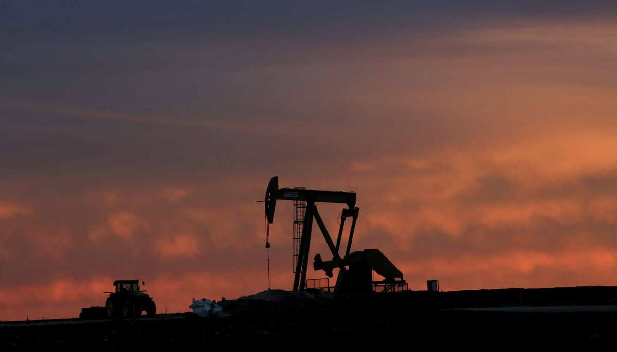 In this photo made Monday, Dec. 22, 2014, a well pump works at sunset on a farm near Sweetwater, Texas. At the heart of the Cline, a shale formation once thought to hold more oil than Saudi Arabia, Sweetwater is bracing for layoffs and budget cuts, anxious as oil prices fall and its largest investors pull back. (AP Photo/LM Otero)